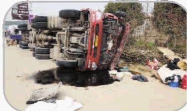 28日上午,侧翻的大货车还躺倒在事故现场,车上的物品和装载的肥料散落一地。 记者 王�鹰 摄