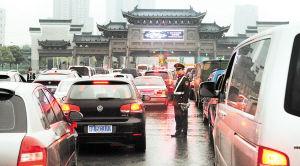昨日,清明小长假在一场阵雨中结束,驾车出门祭扫、踏青的市民踏上返程,下午4时开始,城区各个高速入口出现高峰,堵车现象非常严重。图为工作人员正在雨中进行交通疏导。罗杰科 摄