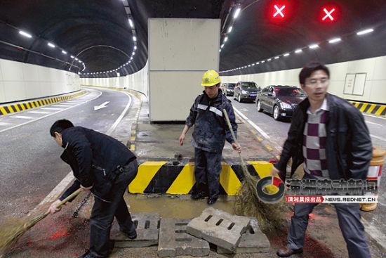 (4月14日,长沙营盘路隧道,工作人员正在排除积水。 图/潇湘晨报滚动新闻记者 华剑)