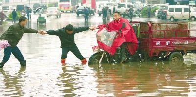 4月15日早上,长沙书院路一低洼地段被雨水淹没,一辆三轮车在水中熄火,两路人一拉一扯,才拉出三轮车。 记者 李丹 摄