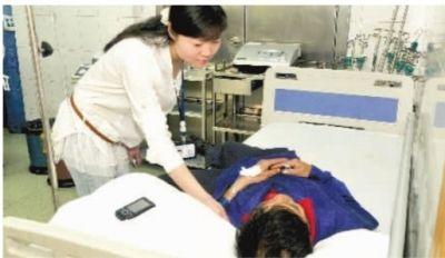 4月24日,长沙市中心医院急诊室,护士朱文青在看望李长端。当日7时许,李长端倒地昏迷,是路过的朱文青救了他。■记者 伍霞 摄