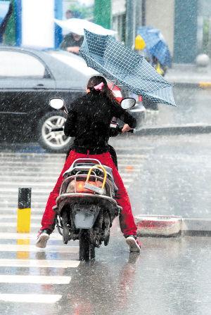 昨日上午,长沙突降暴雨。这是一名市民在晚报大道骑电动车横过马路。图片来源于长沙晚报