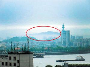 4月30日下午1时,有网友称从书院路拍摄河西交警大楼时,拍到后边出现一片原本没有的山峦。20分钟后,这一奇怪景象消失。 晚报拍客 淳宁 摄
