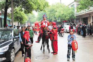骑马抬轿迎亲,吸引了路人的目光。梁露 摄