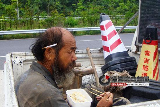 (湖南常吉高速岩门界隧道管理所工作人员,给老人送去吃的。图/潇湘晨报滚动新闻通讯员 黄竹)