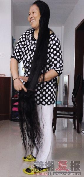 5月16日,邓林萍正在梳理她1.68米的长发。图/巩如泉