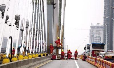 昨日, 银盆岭大桥索塔旁,施工人员开始搭建供工程技术人员上下的脚手架。图/记者华剑