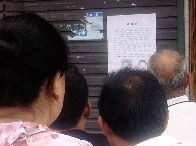 """6月8日,高桥地区物流中心,市民围观""""通缉令""""。图/记者陈斌"""