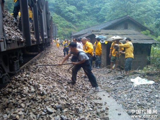 铁路职工正抓紧从抢险车上卸下防洪石碴,填充道床 张宗银摄