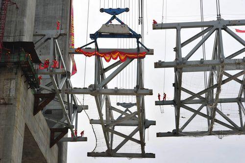 6月11日,施工人员在进行最后一块钢桁梁的合龙对接。湖南日报记者郭立亮摄