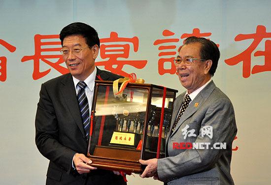 (湖南省委副书记、省长徐守盛和台北湖南同乡会理事长雷玉松互赠纪念品。)