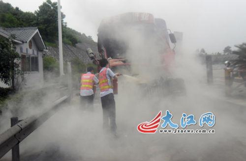 一辆满载货物追尾起火,收费站工作人员帮忙灭火。