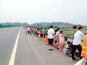 许多村民站在高速公路上看龙舟赛。陈颖 摄
