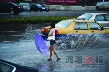 6月27日,长沙市韶山南路,短短10来分钟暴雨过后,路面积水严重,车辆驶过水花四溅。图/记者张轶