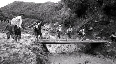 泥石流冲毁了晏子酒家上游约400米处的道路和一座桥。6月30日,当地学生放学后小心地走回家。图/记者周清树