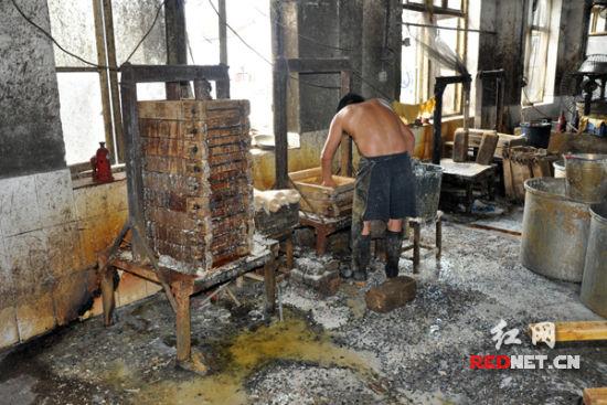 (邵阳帮民食品加工厂厂房里,一名工作人员半裸上阵,周围的卫生环境另人堪忧。)