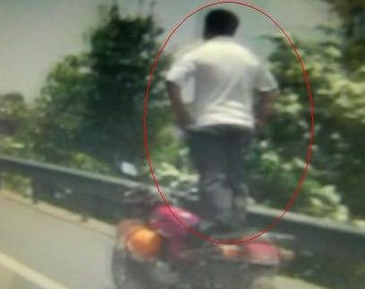 牛司机双手叉腰站着骑摩托车
