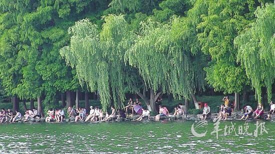 游客在西湖边排排坐泡脚