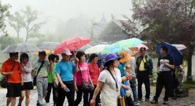 7月13日,张家界武陵源风景区普降大雨。图为游客冒雨游览。 通讯员 吴勇兵 摄