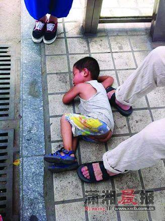 """小孩被抱到路边,一开始很抵触陌生人,最后在地上睡着了。图/网友""""高尚的秦超"""""""