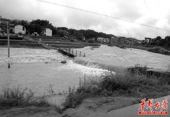 绥宁县降雨量最大的水口乡,农田中的禾苗被洪水淹没,村里通往外界的道路被冲毁,一些房屋摇摇欲坠。通讯员彭超 罗绥峰 陈伟摄