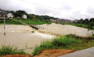 7月15日,湖南绥宁一河道洪水猛涨淹没桥梁,村民无法走到对面的公路上。图/CFP