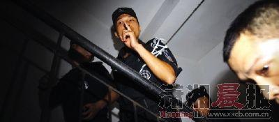 7月12日凌晨,长沙金碧文华小区,警员准备实施抓捕,示意随行记者保持安静。本版图片/实习记者赵赫廷