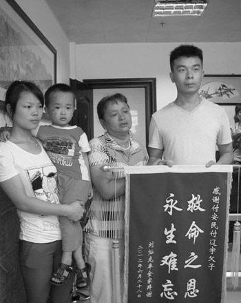 """刘家向付辽宇父子送锦旗感谢""""救命之恩""""。"""