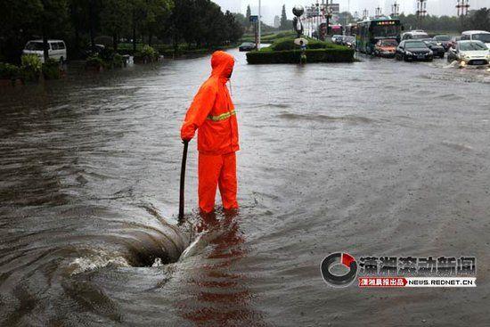 7月16日,株洲市长江广场,市政工人张亮手持木棍站在一处打开的下水井附近。图/记者陈正