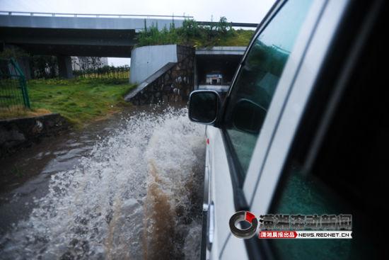 (7月16日,长沙暴雨。图为黎托乡政府附近,一辆车冒险过积水的涵洞。)