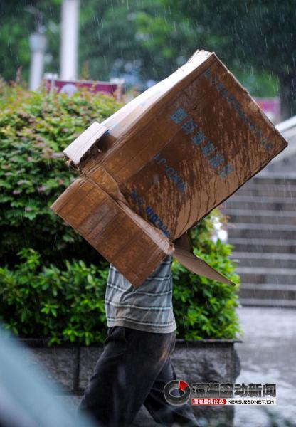 (7月16日,长沙暴雨。上午,湘江一桥附近,两名男子没带伞,一个用纸箱子罩在头上挡雨,另一人用一块泡沫架在头上挡雨。本组图片/潇湘晨报滚动新闻记者 邵骁歆)