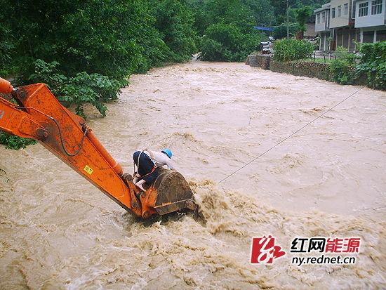 """红网常德7月18日讯(通讯员 张朝晖 赵君)近日,湖南迎来今年以来最大范围强降雨。连日的暴雨把常德澧县甘溪滩的天空砸穿了一个窟隆,瓢泼大雨倾盆而下,溪沟、河流山洪咆哮。从山上冲下来的洪流,使涔河的河水暴涨,超过警戒水位,瞬间对涔河边的电力设备造成严重损坏。      此时,一电杆因暴雨倾斜并产生裂纹,澧县电力局甘溪供电所员工王孝平不畏激流,主动请缨,赤脚爬上机械臂上的挖斗剪断河中的拉线,防止了一起连环倒杆事故的发生。事后,王孝平冒险在挖机上除险的事迹在微博中传播,他勇敢给力的行为获得网友高度认可。网友们给王孝平取名""""最给力的挖斗哥"""",予以赞扬。      """"是供电所吗,涔河边的一根电杆快要倒了,请你们赶紧过来处理""""。澧县电力局甘溪供电所电话响起。汛情就是命令,10分钟后,该所员工王孝平和抢修队伍一起赶到现场。只见电杆已呈40度倾斜并有裂纹,山洪裹着枯藤杂草,不断冲击着河水中的一根拉线,10米的电杆在拉线牵引下不断上下摆动,如果不立即采取紧急处置措施,随时都会发生连环倒杆事故。      当务之急是马上剪断河中的拉线!挖机来了。谁去剪线?""""我!""""王孝平站了出来,主动请缨到河中作业。      带上工器具,王孝平赤脚爬上机械臂上的挖斗,挖斗缓缓向河中移去。滔滔涔河水,狂风卷着大浪,不断拍打着挖机臂,由于挖机臂长度不够,加之风雨中的拉线摇摇晃晃,几次试探,第一次剪线失败。      稍作休息后,王孝平再次爬上挖机。此时的他,做出了一个大胆的决定——先用绳索套住拉线,交给岸上人员牵引,使拉线尽量靠近挖机臂,再剪线。      挖机尽最大限度向前移动。王孝平全身扒在挖斗上,趴低,再趴低。岸上的人心都提到了嗓子眼儿。几番与激流浊浪搏斗后,绳索终于套上拉线,王孝平返回岸上,将绳索交由岸上人员牵引,自己又一次爬上挖机。在众人的努力下,16时10分,王孝平顺利剪断拉线,返回岸上,大家悬着的心终于放下了,而此时的王孝平已是一个泥人,站在雨中喘着粗气。      """"我当时只想防止大范围的电网损坏事故,也没想到自已的行为会被网友关注,这只是我的工作职责。""""事后,王孝平淡定地回忆那一幕。"""