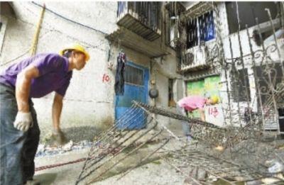 7月24日下午,长沙市开福寺路福源公寓,两名工人在拆卸已搬迁住户的旧防护窗。该公寓目前有不少住户已搬迁。记者 田超 摄