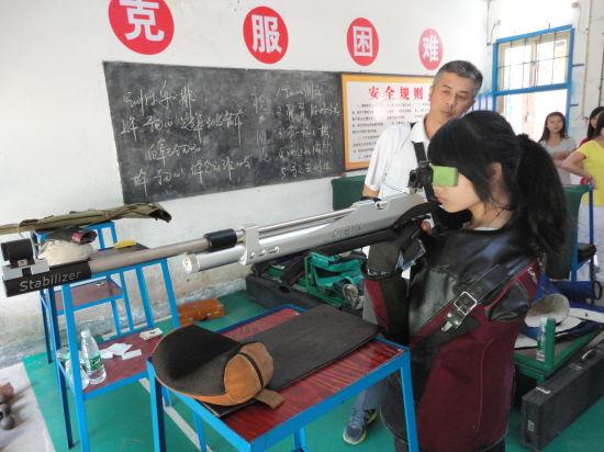 易思玲启蒙教练龙寿柏在教授学生射击