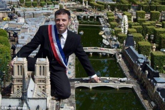 """奥比昂跪在迷你版的""""巴黎圣母院""""前。"""
