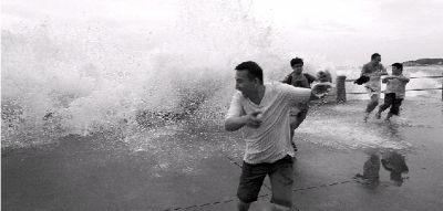 """8月2日,青岛,受今年第10号台风""""达维""""影响,澳门路上大浪冲上人行道,观潮的游人纷纷躲避。中央气象台2日下午发布了今年首个台风红色预警。图/CFP"""