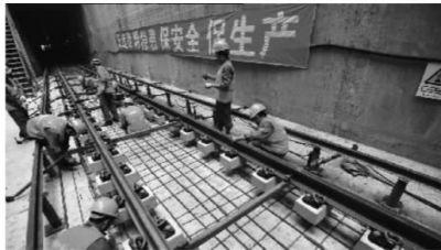 8月3日,长沙市长沙大道地铁站施工现场,施工人员正在地铁隧道内铺轨。 记者 李丹 实习生 李际 陈俊筱 摄