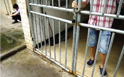 8月4日,一名同学从楼上下来,门是锁着的,负责开门的保安就在旁边坐着。图/实习记者李坤