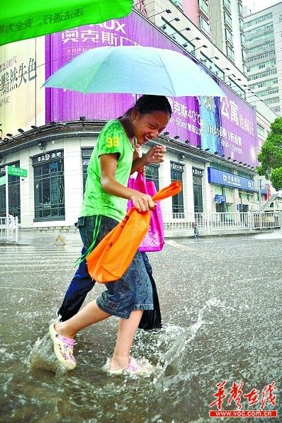 ▲雨才下了几分钟,局部地区积水就达到了5厘米深,两个女孩走过,积水溅起水花。实习生 唐俊 摄