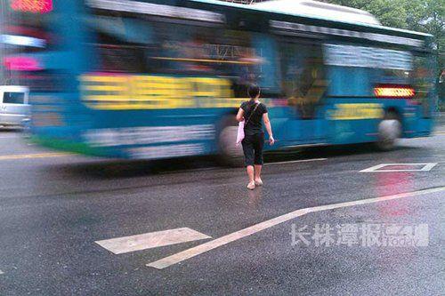 (8月9日清晨6点半左右,株洲市芦淞区建设南路江南商城前,一市民横穿马路。前一天上午九点左右,这里发生车祸,一名骑自行车女子被撞身亡。图/长株潭报滚动新闻记者 曾永红)