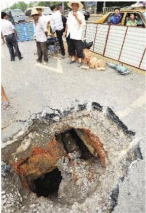 香樟路路面塌陷的大坑,引来许多路人张望。记者 童迪 摄