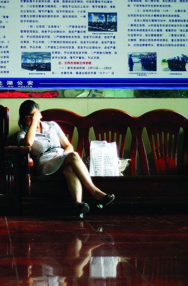 8月10日 郴州市公安局北湖分局。经过两天庭审后,卖肾孩子的妈妈疲惫地瘫坐在公安局休息厅里。 图/记者赵赫廷