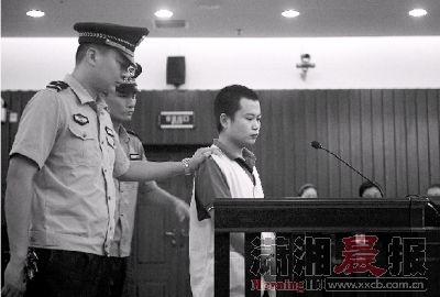 昨日,21岁的邓少华在法警的押解下离开庭审现场。图/记者张轶