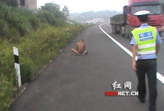 (男子盘腿坐在高速公路路肩上,民警将其安全带离并护送回家。)