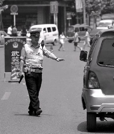◀8月11日中午12点半左右,重庆市歌乐山镇歌乐山街,交警持枪搜查过往的车辆。 图/记者刘有志