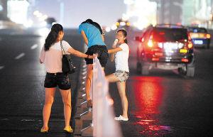 昨晚,不断有行人冒险从五一大道翻越护栏横穿马路。   小刘军 摄