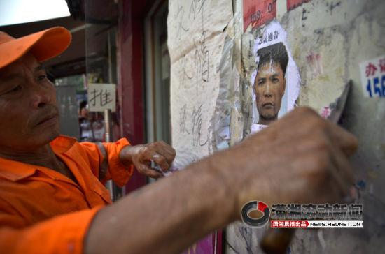 (8月15日,张贴在长沙大街小巷的周克华通缉令正在被清除。图/潇湘晨报滚动新闻实习生 胡冬冬)