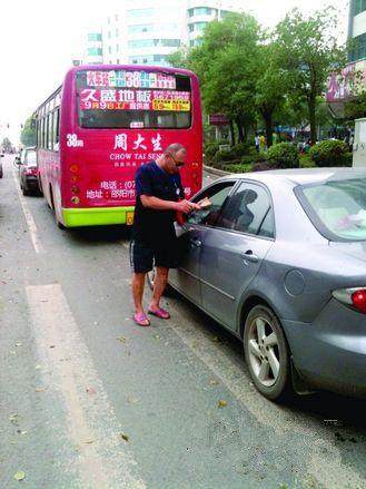 8月17日,邵阳市西湖路与宝庆路交接处,穿拖鞋戴墨镜的市容监督员在对占压斑马线停放的车辆罚款。图/记者龙源