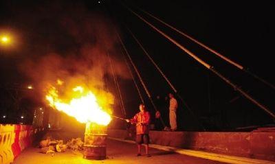 8月25日,银盆岭湘江大桥完成更换60对斜拉索工作,工人们在桥上用焚烧的方式清理包装纸皮。图/实习生杨旭