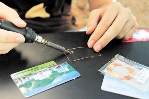 """组装""""万能手机""""的关键步骤是把电焊挂一点点焊锡小心地焊在芯片线圈两个金属引脚上。"""